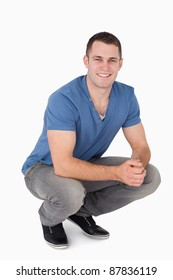 Portrait of a man squatting against a white background