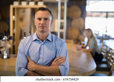 Portrait of man standing with arms crossed near bar counter