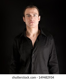 A portrait of a man standing isolated on black background