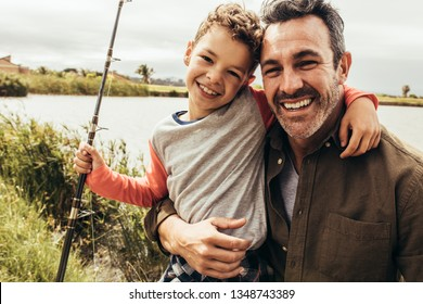 Portrait of a man standing on the banks of a lake with his kid holding a fishing rod. Smiling father and son standing near a lake holding each other.