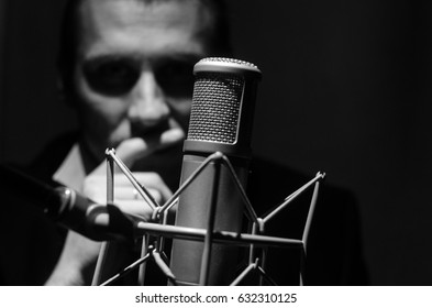 Portrait of a man with studio microphone. Black-and-white horizontal photo