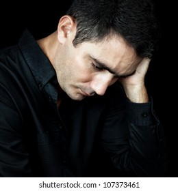 Portrait of a man suffering from a strong headache or depression isolated on black