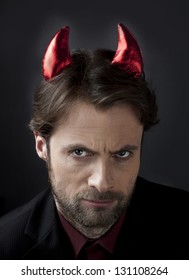 Portrait of a man in suit with devil horns. Concept of a nasty, cruel, scary, demanding boss or symbol of unfair competition in business.