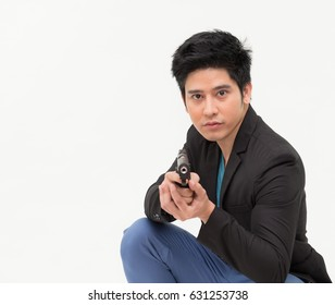 Portrait of a man in suit holding gun against a grunge background,Image of a confident handsome policeman holding a handgun,Businessman takes to gun to protect his business,Age 20-30 yeas