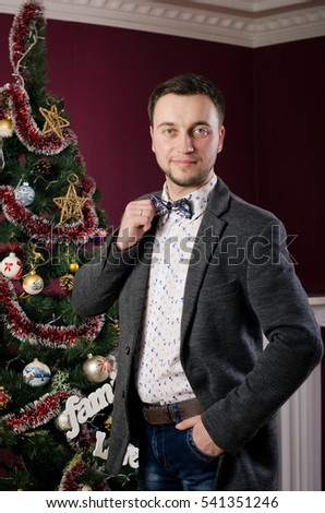 portrait of a man in a suit near a christmas tree and fireplace