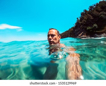 Portrait of a man swimming in turquoise water near rocky coast