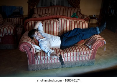Portrait of man switching TV channels on sofa at night