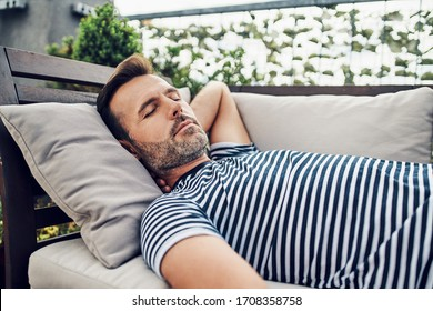 Portrait of man taking nap on apartment terrace