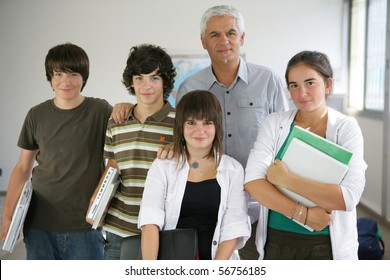 Portrait of a man and teenagers holding documents in a classroom