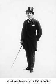 Portrait of a man in a top hat and morning suit holding a cane