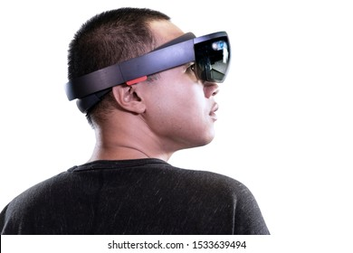 Portrait of man try Mixed reality with HoloLens glasses isolated on white background. Future Technology concept.
