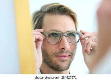 Portrait of man trying eyeglasses on in front of mirror