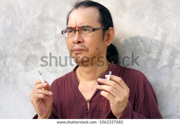 portrait of man with two cigarettes