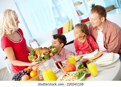 Portrait of man and two kids looking at roasted turkey held by happy female