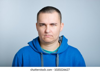 portrait of a man unhappy, wearing a blue hoodie, isolated on a gray background