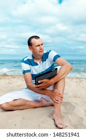 Portrait of man using tablet computer in  coastline,