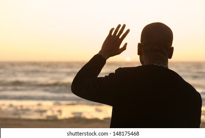 Portrait of a man waving at the sunset