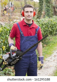 portrait man wearing  ear protectors trimming the bush in the backyard with petrol  bush trimmer