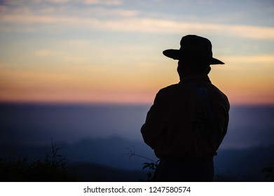 Portrait of a man wearing a hat Looking at the mountains in the evening.
