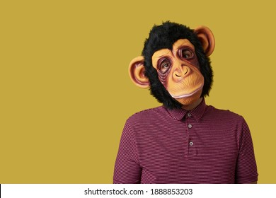 portrait of a man wearing a monkey mask on a yellow background with some blank space on the left