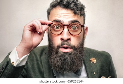 Portrait of a man wearing retro style glasses. He is in shock.