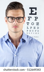 Portrait of man wearing spectacles with eye chart in background