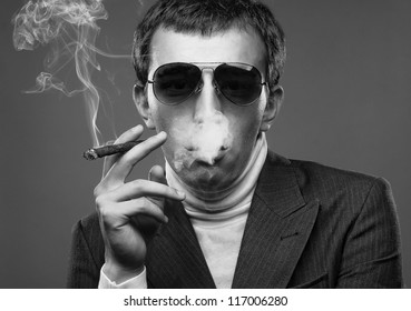 portrait of a man wearing sunglasses and smoking a cigerette.