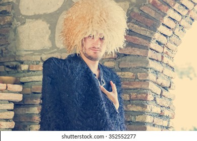Portrait of man wearing traditional felt cloak and fur cap in stonewall interior