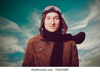 Portrait of man wearing vintage style aviator cap and goggles with retro filter against blue sky