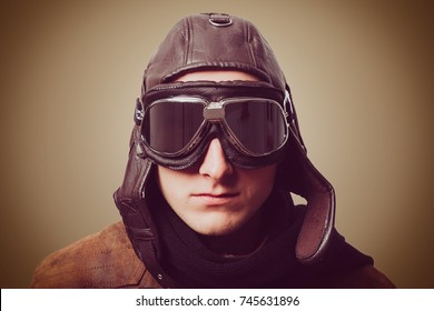 Portrait of man wearing vintage style aviator cap and goggles with retro filter