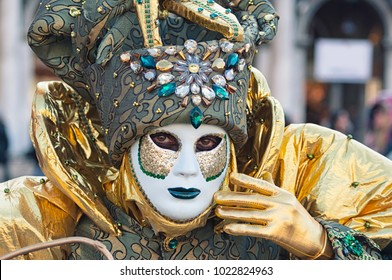 Portrait of a man wearing a white and green mask during the Venetian carnival party in San Marco square, Italy