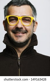 Portrait of a man wearing yellow glasses and smiles. Studio shot. Grain added.