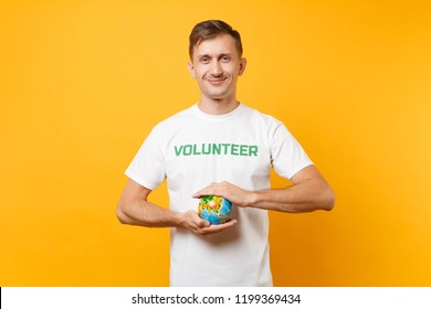 Portrait of man in white t-shirt with written inscription green title volunteer holding in palms Earth world globe isolated on yellow background. Voluntary free assistance help, charity grace concept
