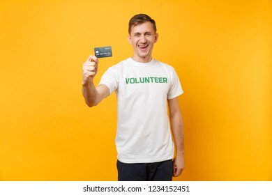 Portrait of man in white t-shirt with written inscription green title volunteer hold in hand credit bank card isolated on yellow background. Voluntary free assistance help, charity grace work concept