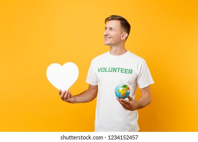 Portrait of man in white t-shirt with written inscription green title volunteer hold blank heart, Earth world globe isolated on yellow background. Voluntary free assistance help charity grace concept