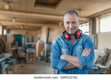 Portrait of a man who owns a small carpentry business, standing in his workshop with with arms folded and showing strong forearms, smiling confidently at the camera. Carpenter posing on his workplace