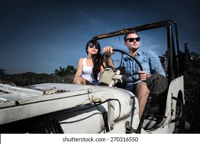 portrait of man and woman driving a 4 wheel drive car cross country. adventure