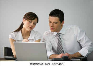 Portrait of a man and a woman in front of a laptop computer