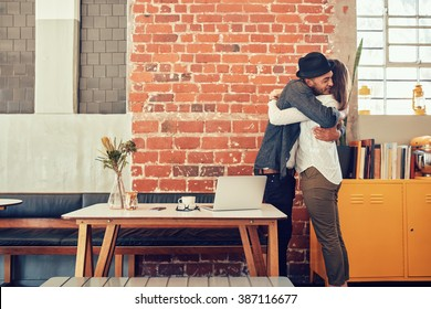 Portrait of man and woman hugging and greeting each other at a coffee shop, couple meeting in a cafe.