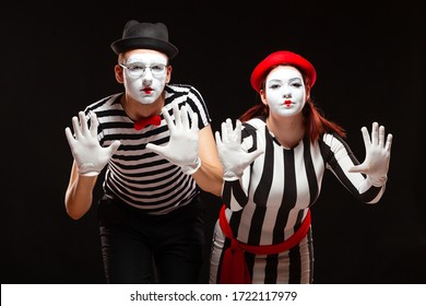 Portrait of man and woman mime artists performing, isolated on black background. Mimes in striped clothes pretending to be behind the glass - Shutterstock ID 1722117979