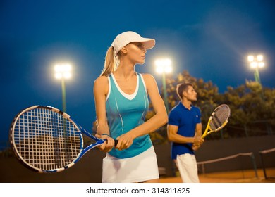 Portrait of a man and woman playing tennis at night