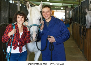 Portrait of man and woman with roan horse at horse stable
