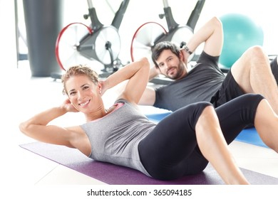 Portrait of a man and woman training together at the gym. Personal trainers doing sit-ups at fitness room.