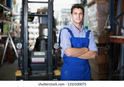 Portrait of man worker in uniform  standing near shelving in building workshop