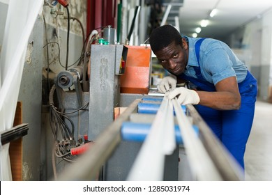 Portrait of man worker who is occupation near special machine in the pvc workshop.