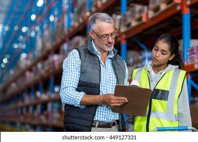 Portrait of manager is showing a clipboard to a worker in a warehouse