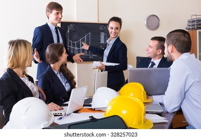Portrait of managers and workers with helmets and laptops having meeting
