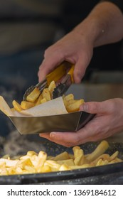 portrait of man's hand serving fish and chips