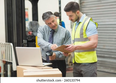 Portrait of manual workers scanning package in the warehouse
