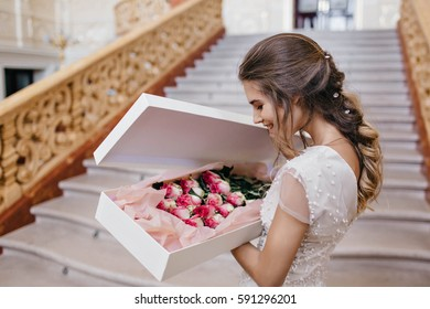 Portrait marry young woman in white dress, with light hairstyle holding pink roses in box in vintage apartment. Stairs, happiness, gift, gratulations, preparations, smiling